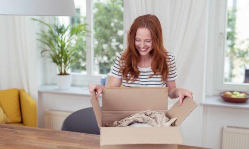 frau packt zuhause ein paket aus